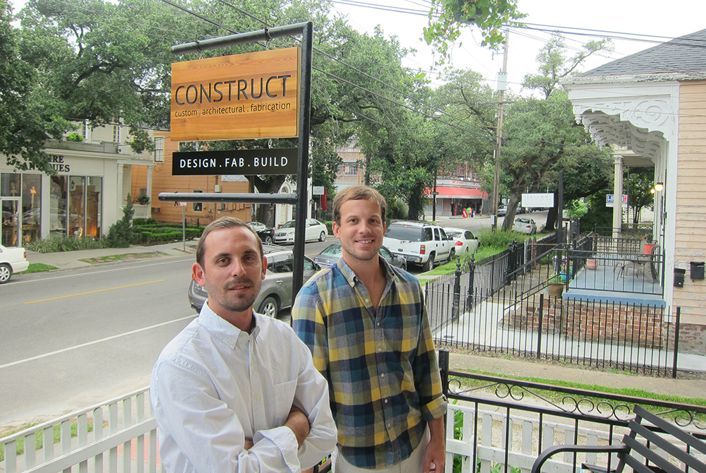 Two men by Construct sign