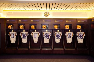 LSU football jerseys and helmets hang in row on wall
