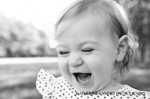 Black and white photograph of a little girl laughing
