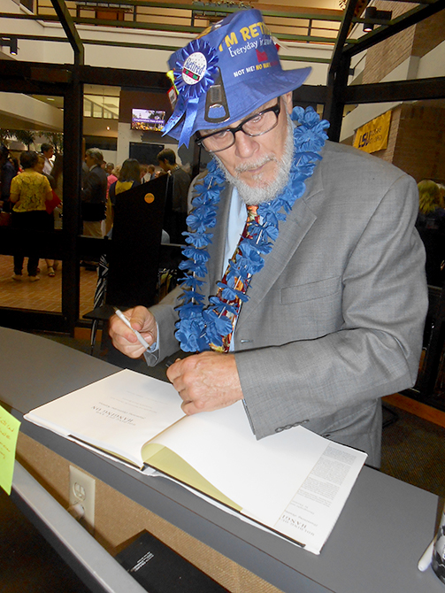 Thomas Neff signs a copy of his book, Holding Out and Hanging On: Surviving Hurricane Katrina