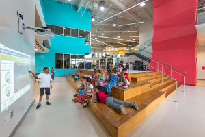 colorful elementary school space with wooden stairs, lsu interior design alumni work