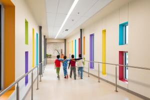 Children walk down school hallway with colorful window frames