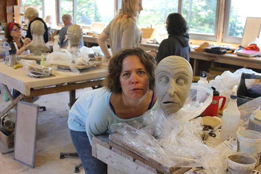 Woman mimics facial expression of ceramic face
