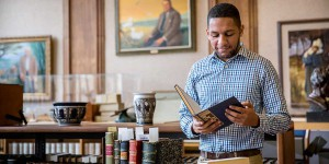art history graduate Glauco holds book in library