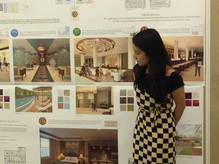 Young woman in checkered dress presents work. lsu interior design student work