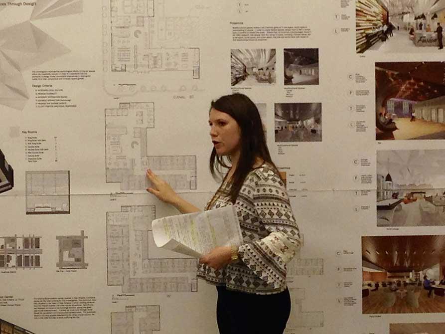 Girl points at floorplan on wall. lsu interior design student work