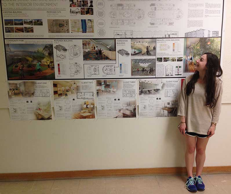 Student by wall of work. lsu interior design student work