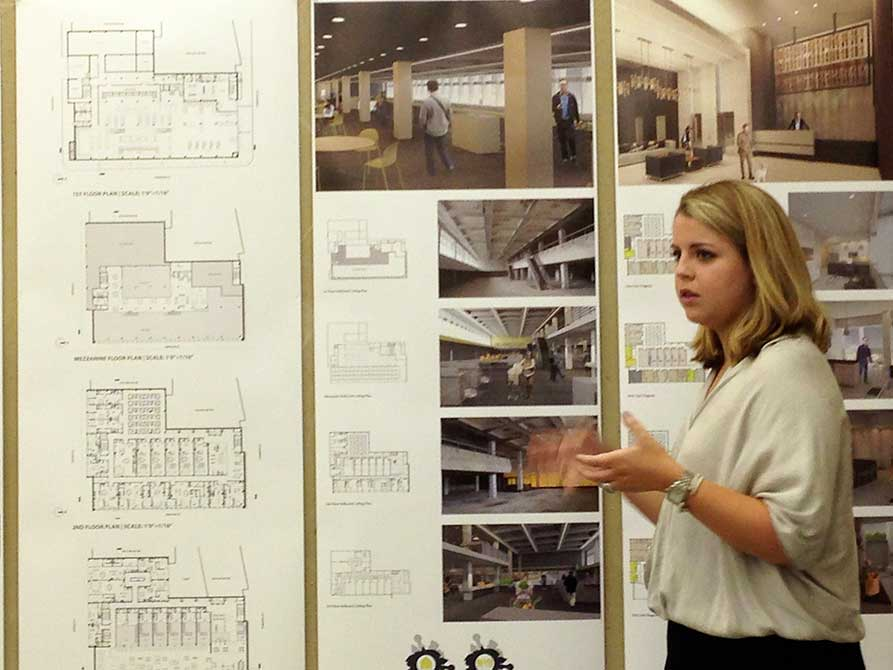 Student gesticulates as presents work. lsu interior design student work