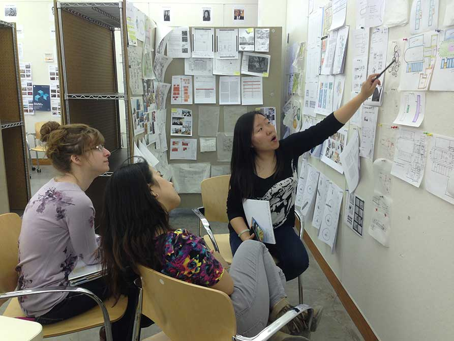 Young woman points at board. lsu interior design student work