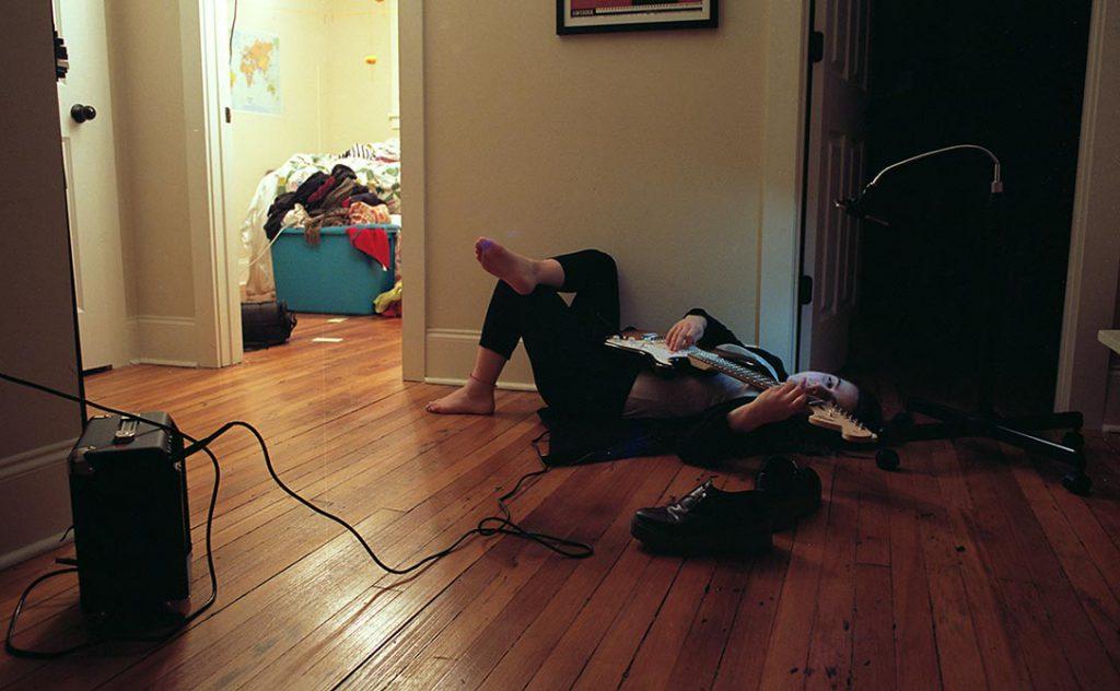 Girl lying on floor playing guitar. lsu photography student work