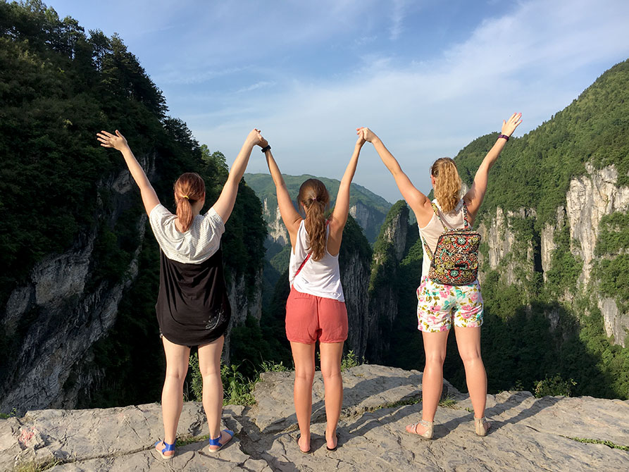 Girls raise arms in front of cliffs
