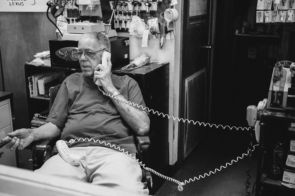 An old man talks on the telephone in his office