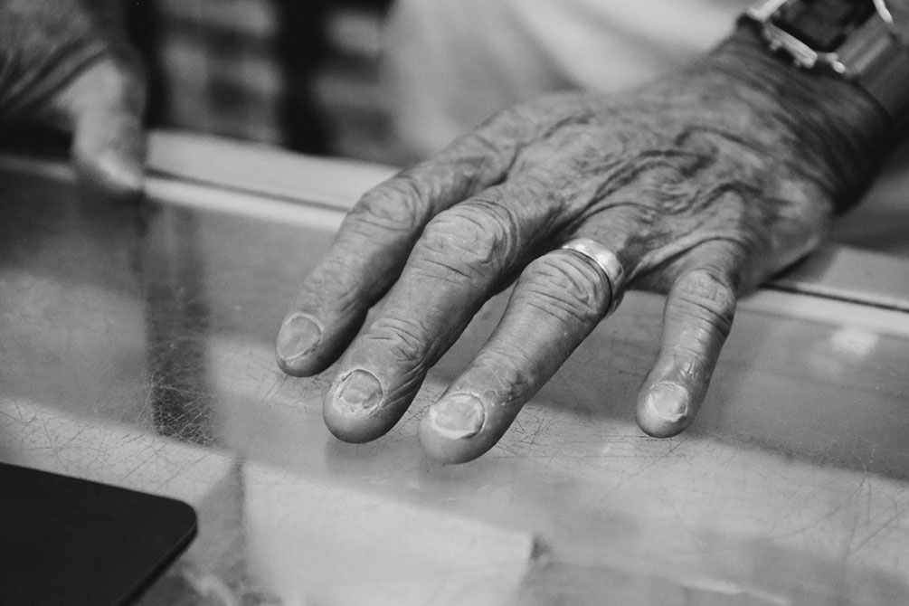 An old wrinkled hand rests on a table
