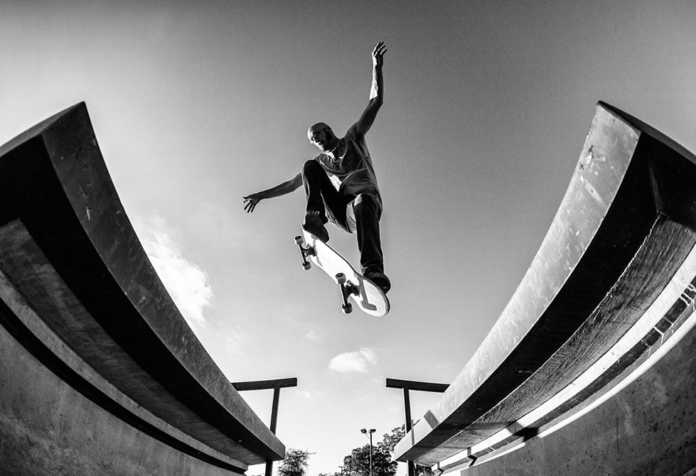 Black and white photo man jumping skateboard