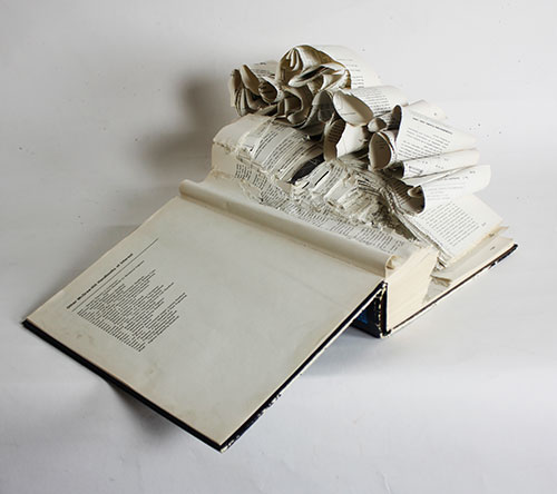 Book with pages ripped into model of glacier