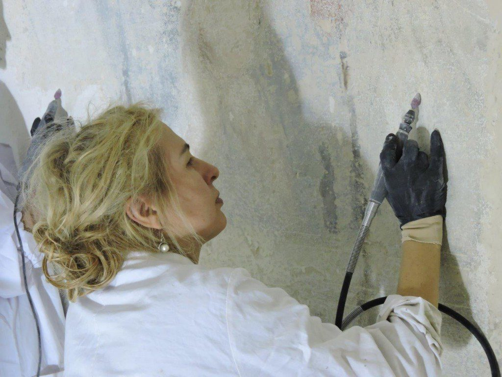 Elise works on wall with tool