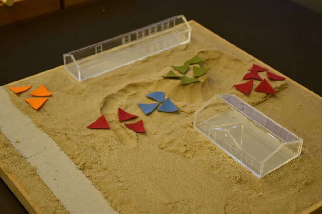 Players sculpted a sand model to create swales and planted trees using triangular patches of felt.