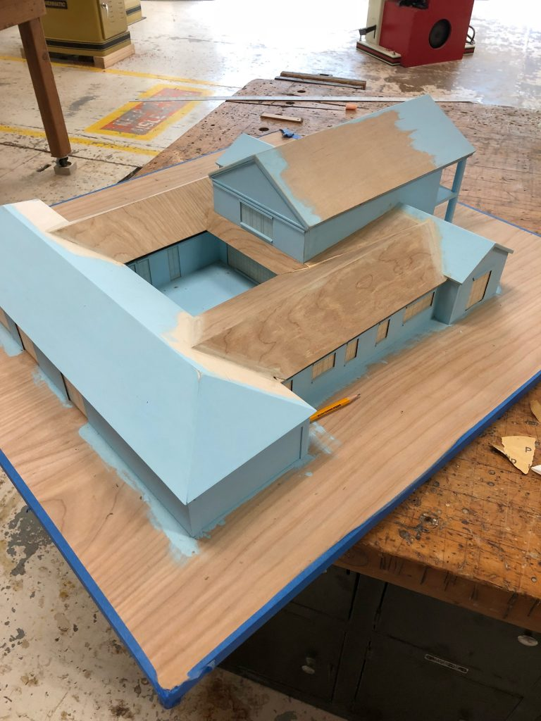 Wooden model of house being painted blue