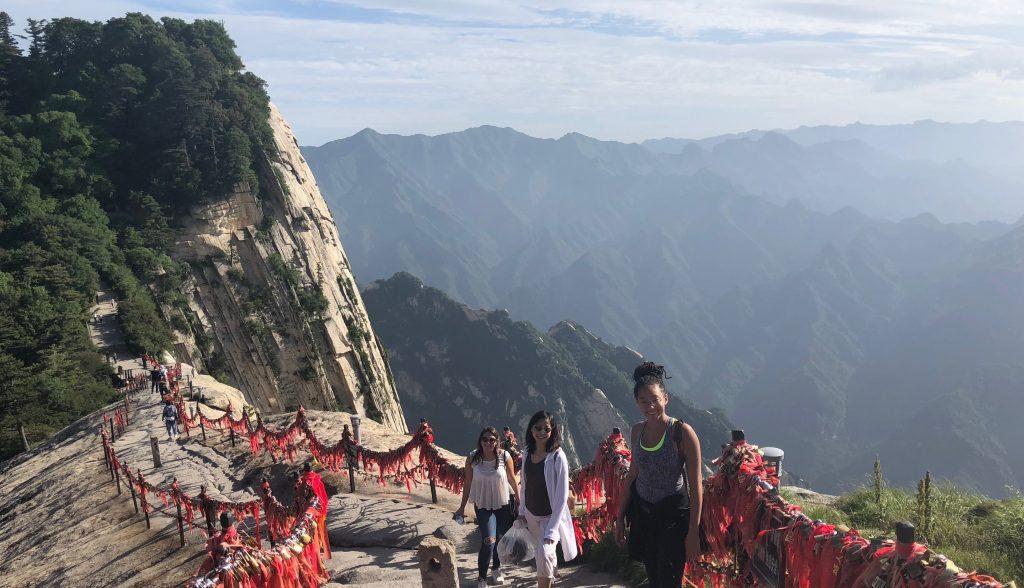 Three female students hike mountain trail in China