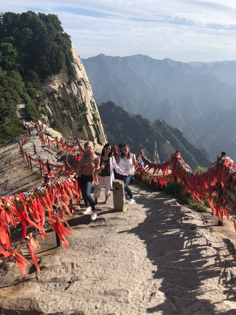 Students hiking to peak of chinese mountain on pathway with red fabric lining the fence