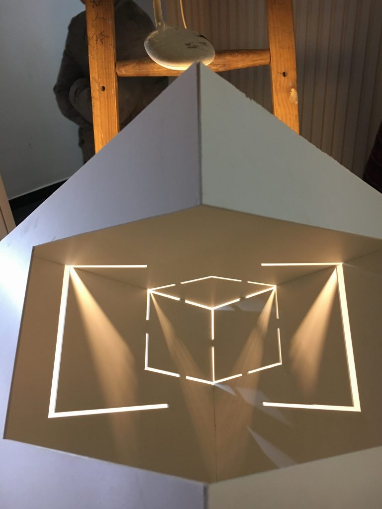Abstract deisgn of lighting in a square existence surrounded by cardboard