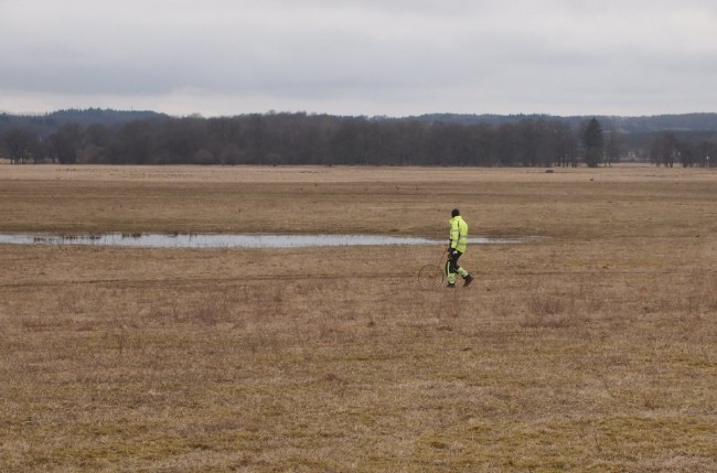 Man in high visibility jacket marks out distances on a site