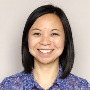 Portrait of Elaine Yau smiling in a blue shirt