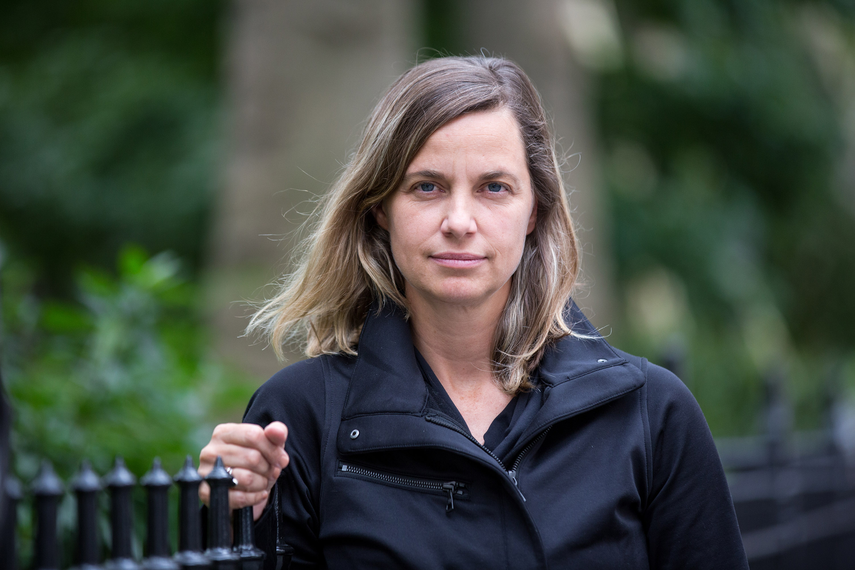 Portrait of Kate Orff leaning on fence