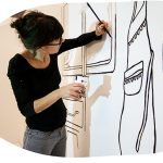 Paula Troxler paints and image with black lines on a white wall