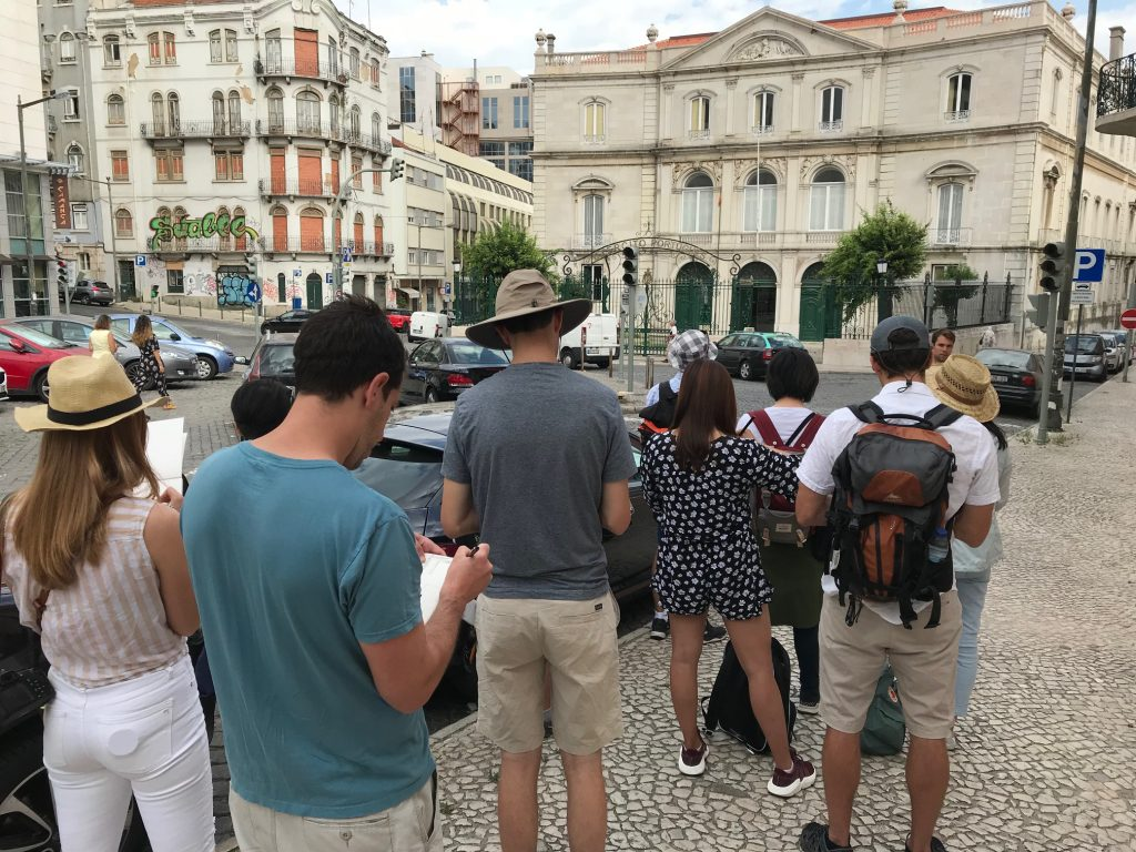 Group of students sketching a building in a Lisbon plaza
