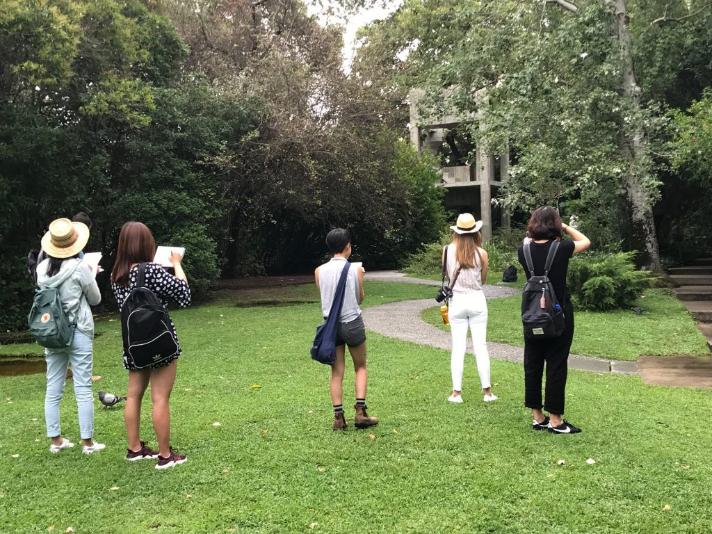 Five students sketch while standing in a park