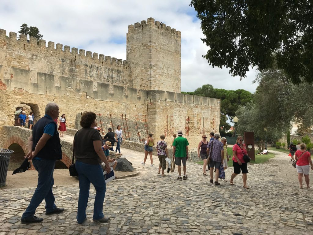 People walk up a ramp into a castle