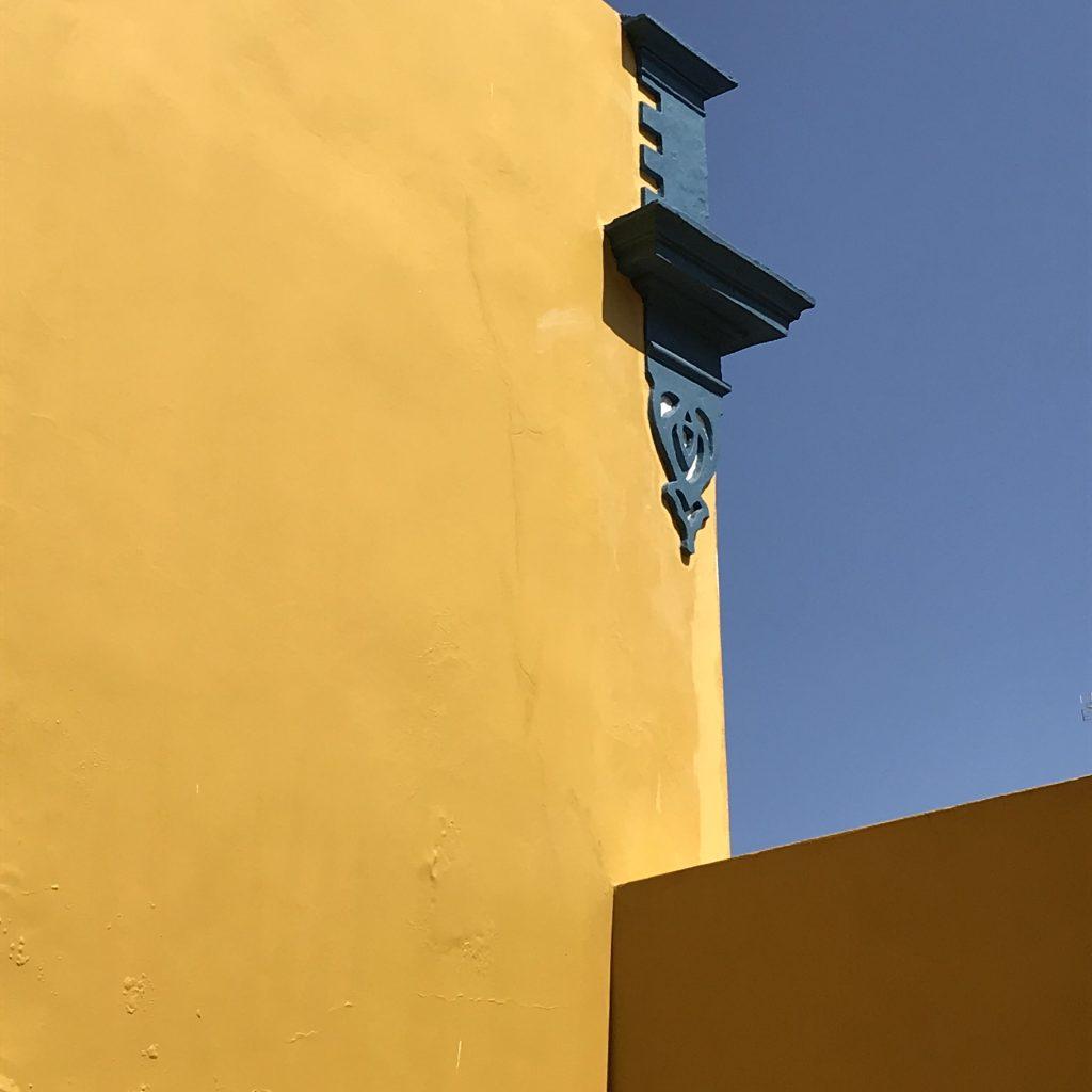 Corner of orange building against blue sky
