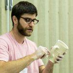 Doug Peltzman holds a ceramic cup in his hands
