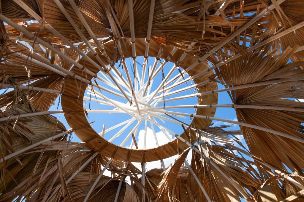 Opening in roof of palm hut shows blue sky above