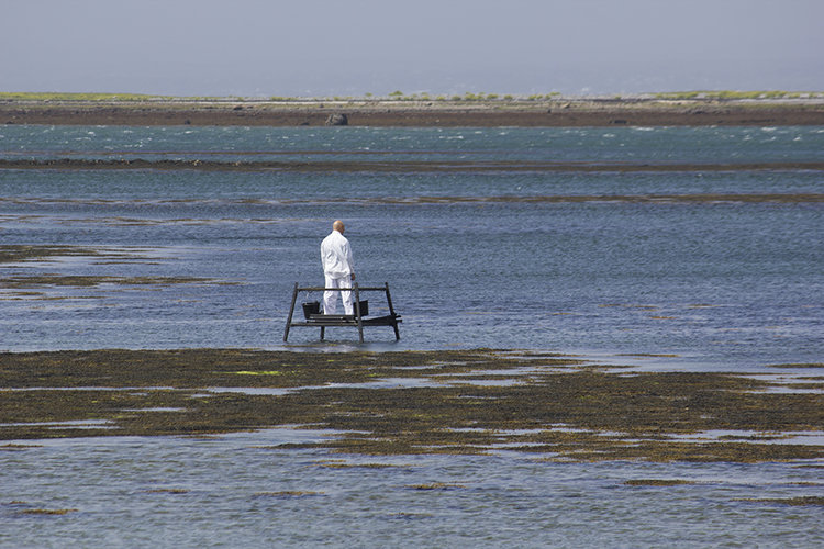 Man in white clothing stands on platform in the ocean