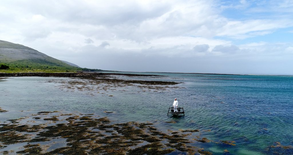 White figure stands on platform in ocean