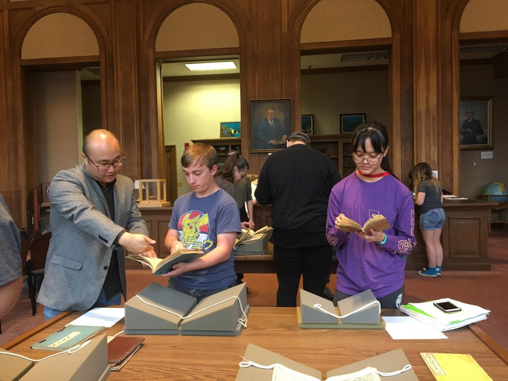 Professor and two students look at books in library