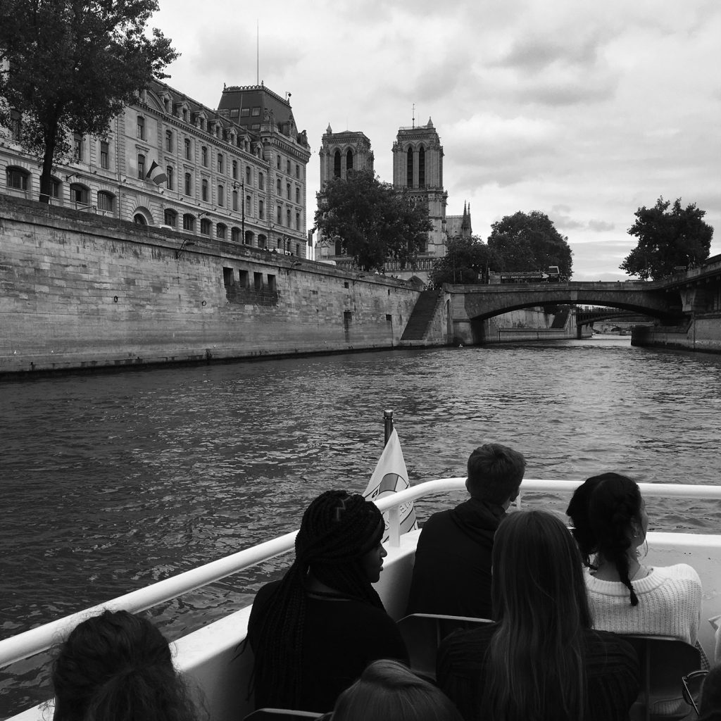 Students in boat, Notre Dame on shore. Black and white photograph