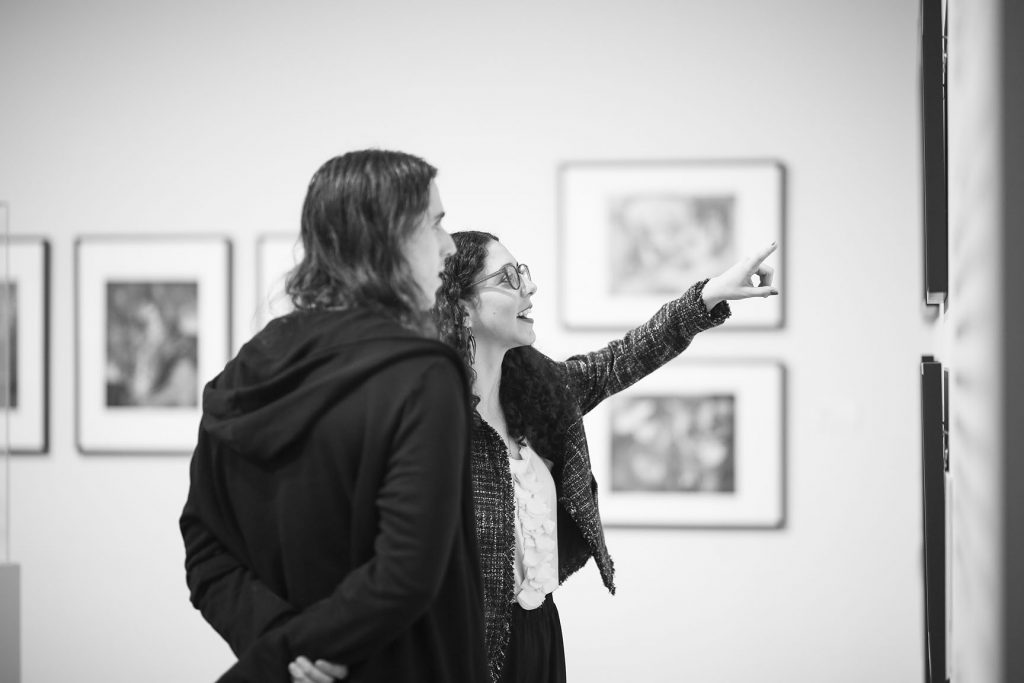 Black and white photo of student pointing at art in museum