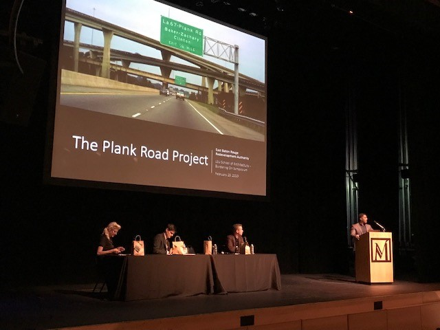 "Man stands at podium. Screen displays words ""The Plank Road Project, East Baton Rouge Redevelopment Authority."""