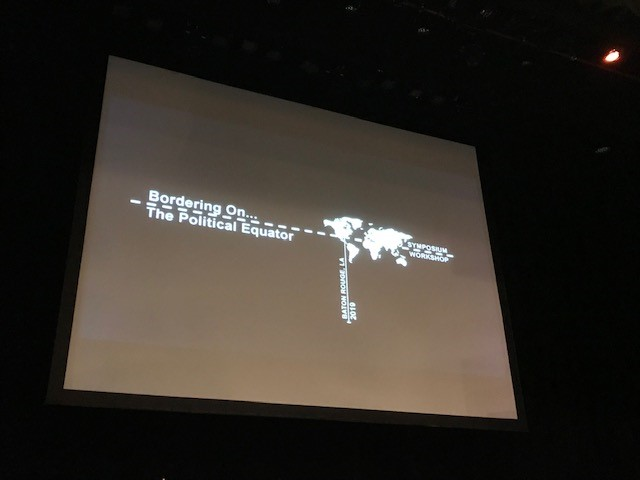 "Screen reads ""Bordering On Symposium & Workshop, Baton Rouge, LA -2019"" with image of world map."