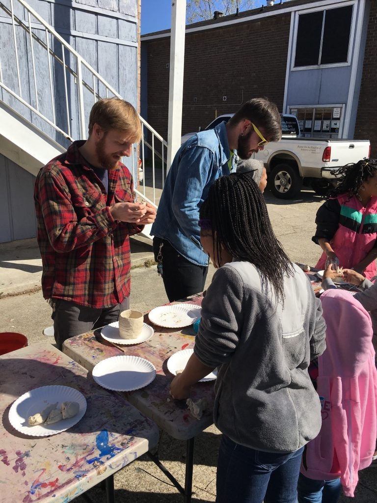 Student in plaid shirt sculpting with clay