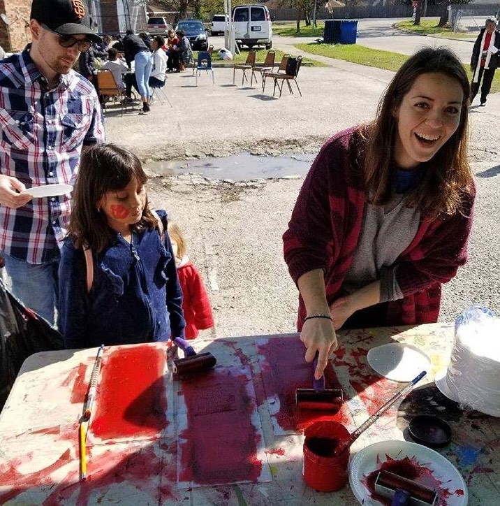 Female student laughing, rolling red paint