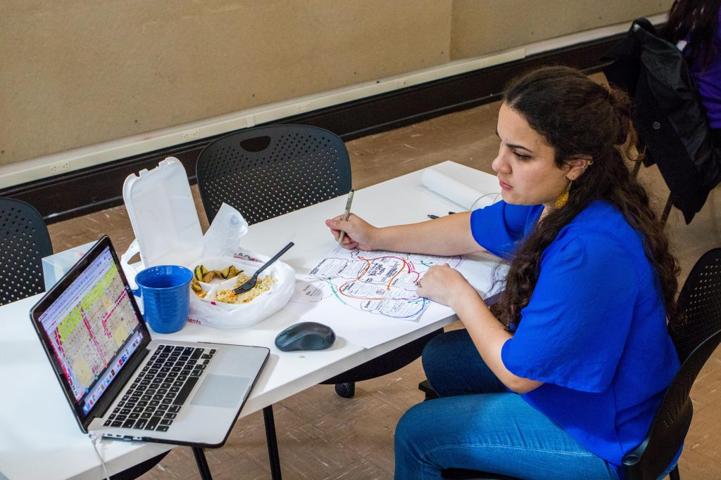 Female student in blue shirt at laptop.