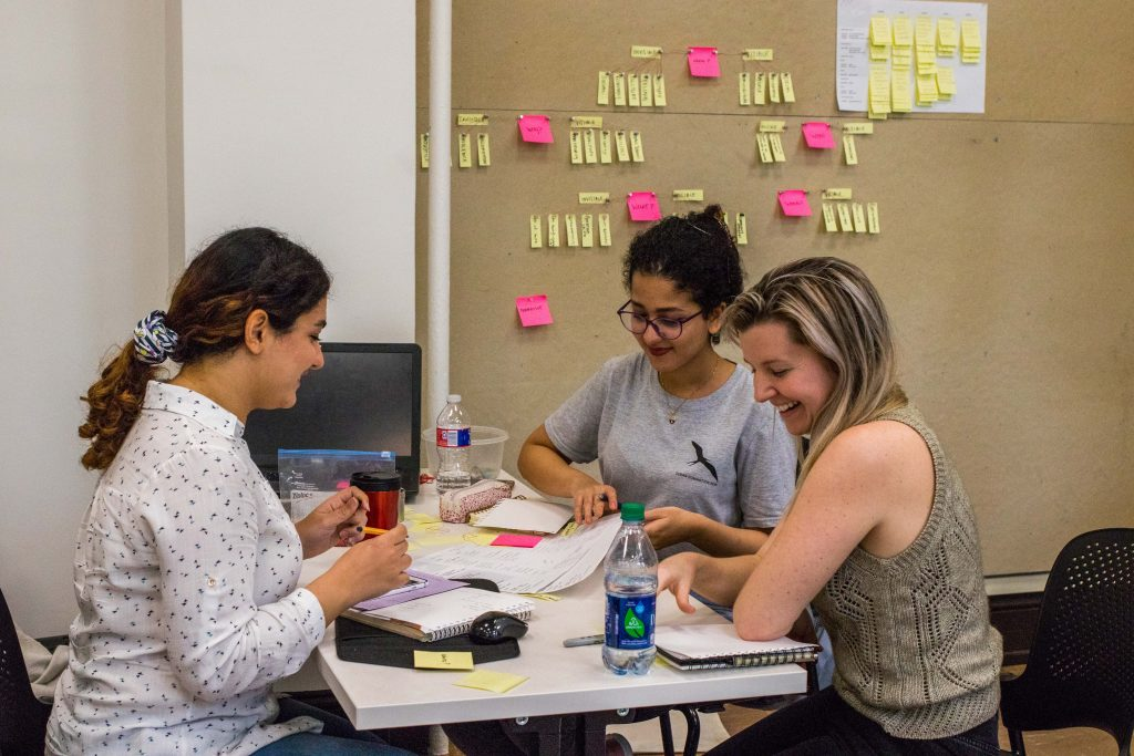 3 female students smiling. Board on wall displays yellow and pink post-it notes.