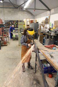 Girl welding, shooting sparks