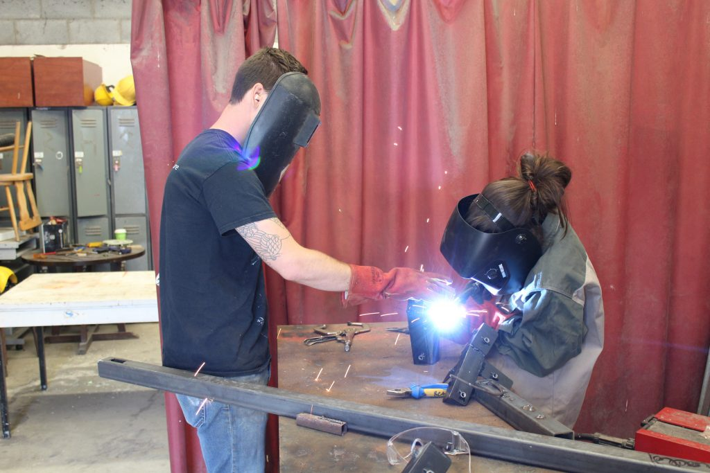 Two students with masks welding in shop