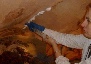 Woman inserts foam into cracks in mural