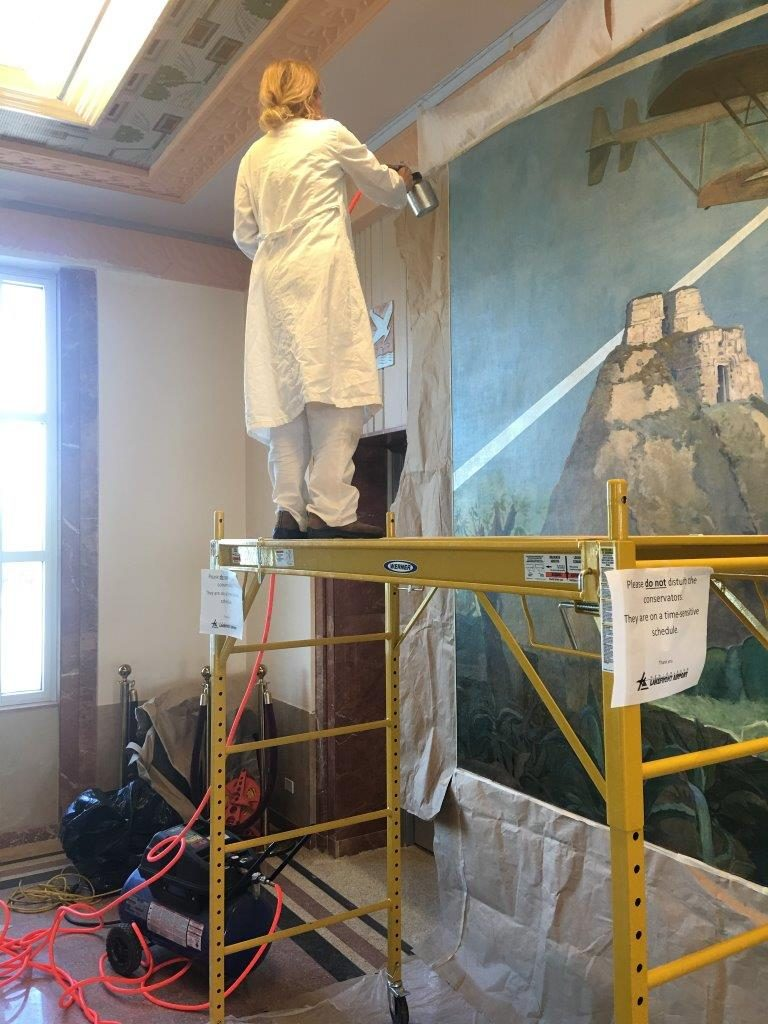Elise stands on scaffolding to work on mural restoration